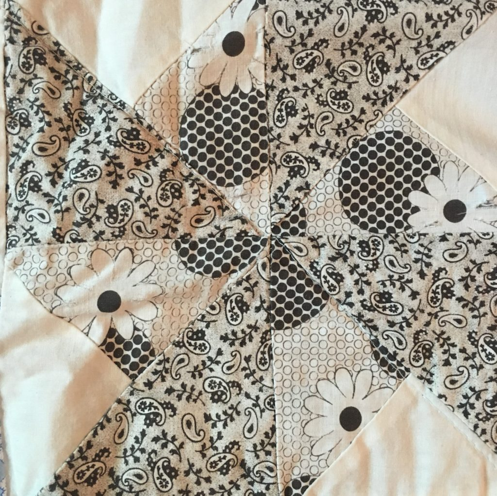 Black and white double pinwheel quilt block, part of an entire quilt made of depression era prints